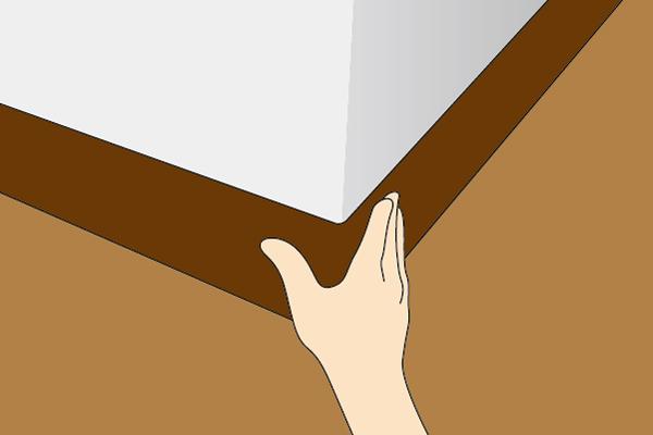 巾木を若干引き伸ばしながら角に当て手で押さえる